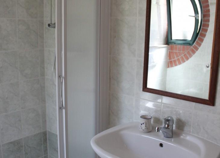 Bagno con doccia di una camera tripla.
